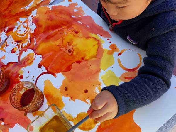 child painting with orange color